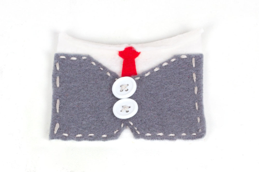 Step 2: Take the white piece of felt and either stitch or glue the red tie shape onto it (underneath the collar). Stitch the white buttons onto the centre of the grey felt shape, then sew the grey and white pieces together (grey on top).