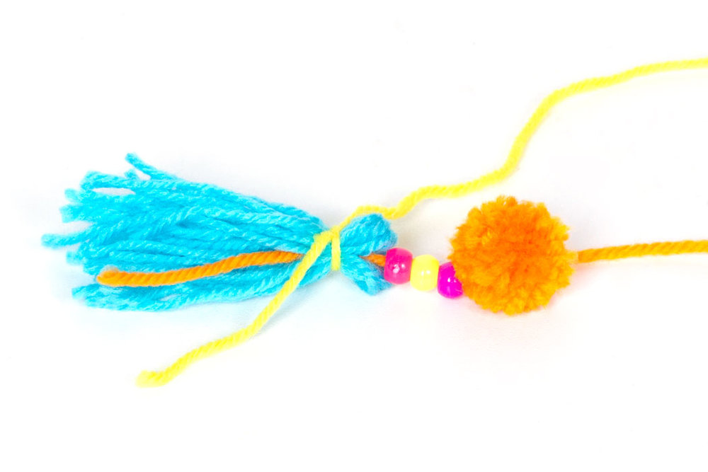Step 3  Thread some colourful pony beads onto one end of the orange wool that is attached to the pom pom. Then hold all of the blue pieces of wool together and fold in half. Add the end of the orange wool to the folded blue wool, and then tie it all in place with some yellow wool as shown in the photograph above. Once the wool is tied in place you can trim the orange end so that it doesn't show in the tassel.  Finally, wrap the end of the yellow wool around the tassel about six times and tie in place at the back. Then tie the other end of the orange wool (attached to the pom pom) to the metal keyring and your keyring is finished!  Subscribe to my  newsletter  to receive fun craft ideas and freebies!  Please note: this blog post contains affiliate links, however all opinions are my own and I only link to products that I personally recommend.