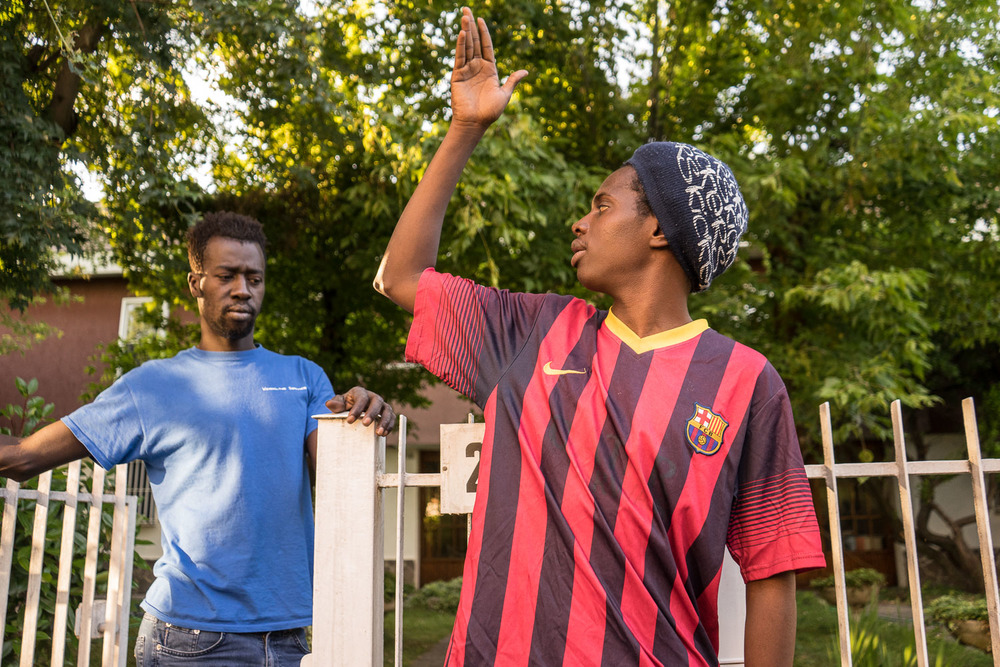 """People at home are depending on me.""  Faburama Bojang (26), in background (left) listens to Mohamed Jallow (25), in the foreground (right).   Faburama from the Gambia lived and worked in Libya from 2008 to 2011 before returning home when the Gaddafi was ousted, killed and the country plunged into civil war. Returning in 2014 to find a lawless place, Faburama left by boat for Italy.  Mohamed says, ""When I was in The Gambia, I could help my family.  I was expecting, by now, to be free.  To be free to go where I want to go in Europe.  There are many things I could have done in this time.  But instead I have not been able to do anything.""  There is a sense of uncertainty, frustration and sadness in the house."