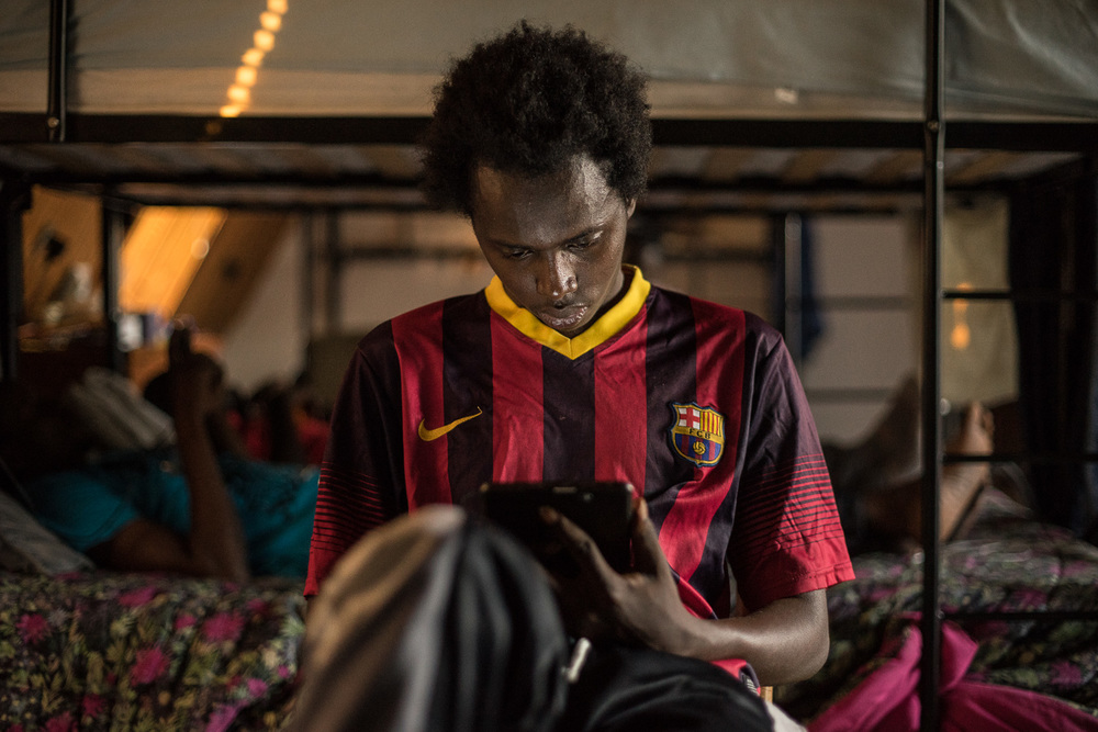 """I consider myself very lucky to be alive.""  Mohamed Jallow (25) reading in his dormitory room.    Mohamed has been waiting for documents since arriving in Italy by boat on October 2nd, 2014. ""I want to study journalism in Europe and report on global issues."""