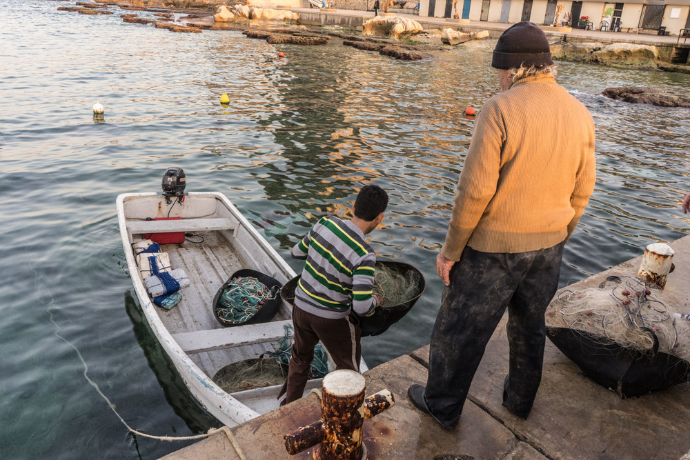 Khalid (15) and Abu Eassa (71) load a boat to go fishing.  Abu Eassa is one of the most experienced fishermen in Beirut having fished the waters for over 40 years.