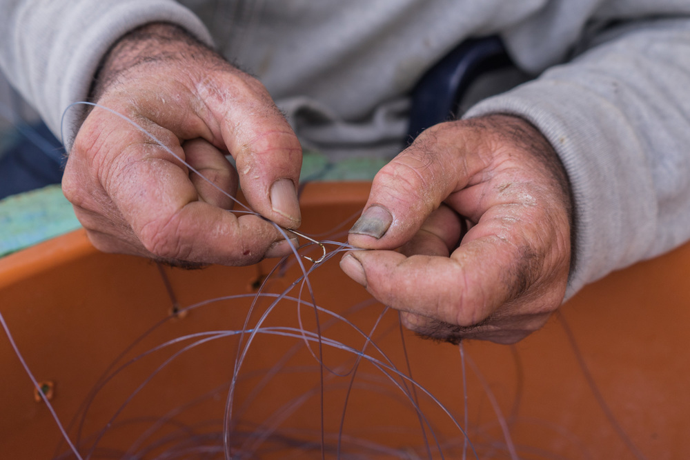 Abu Eassa's hands are worn and rough from years of working the sea.  Here he ties hooks to a line.