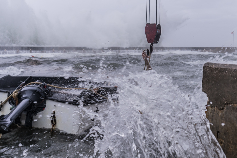 During a storm, Khaled helps remove a damaged boat from the harbor.  Khaled's hand can be seen above a wave crashing against the harbor wall.  A scientific study by the  Universidad de Cádiz, Spain found that concentrations of plastic in the Mediterranean Plastic were dominated by millimeter-sized fragments.  The research showed a higher proportion of large plastic objects than that present in oceanic gyres, reflecting the closer connection with pollution sources.