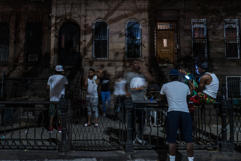 People congregate outside the Slaughterhouse before a dance battle event.  Fatboy (white vest and flip flops) was born and raised in this Brownstone building.  With rents rising rapidly and the price of property meaning low income families are unable to start families, the neighborhood is gentrifying.