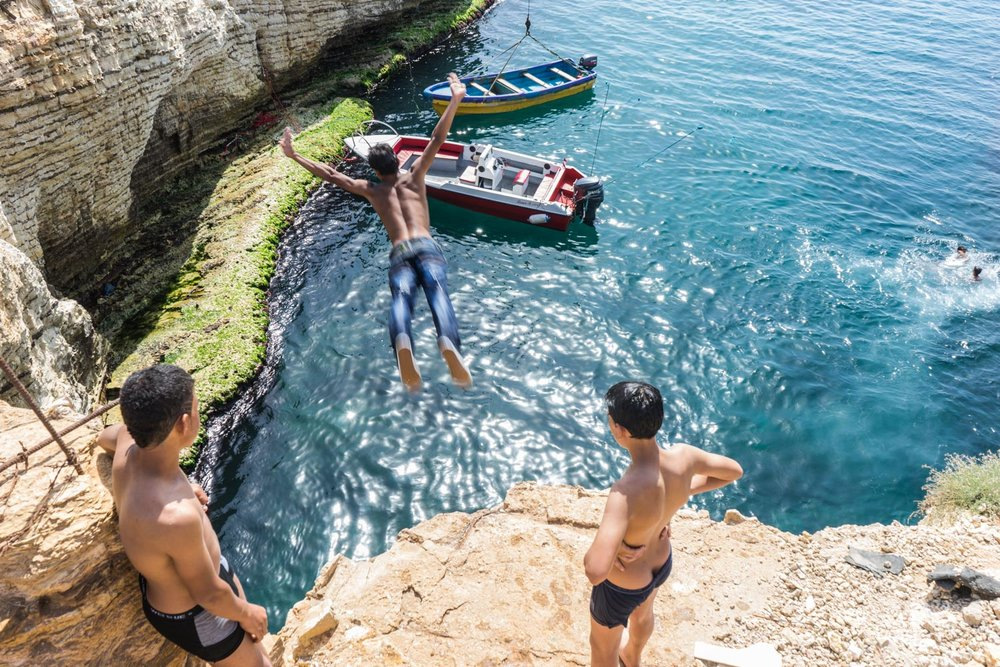 Khaled (15) dives off rocks as friends look on near where he is learning to live off the sea.