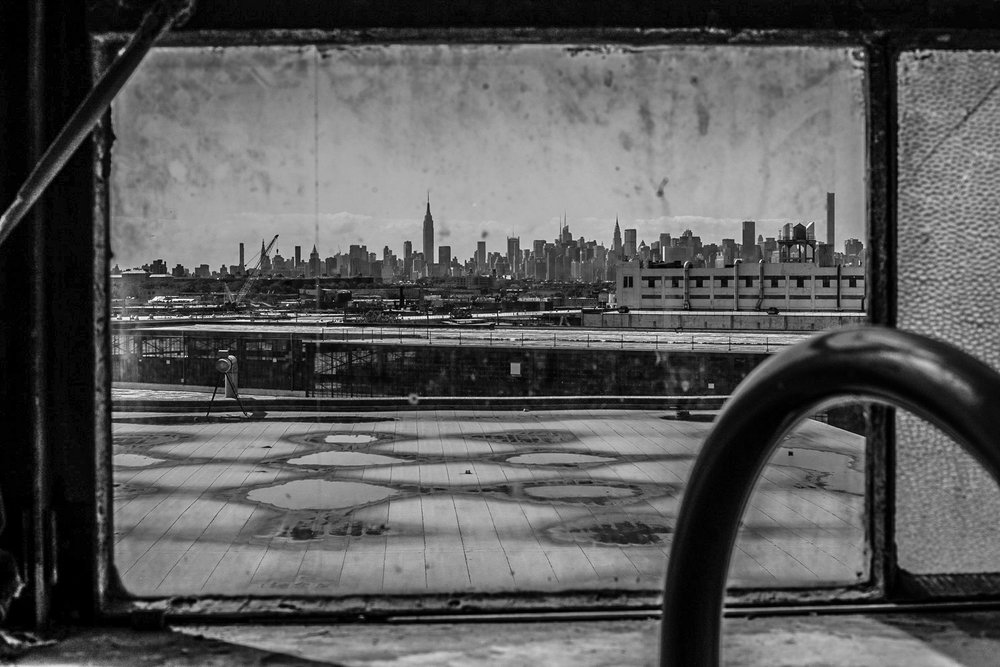 "The Manhattan skyline is visible in the distance from the roof of the boxing gym in Brooklyn.  New people are moving into the area, often with higher incomes.  ""Rent is crazy bro"", says Nate.  ""I don't know how long more I can stay here"".  Nate hopes that boxing will help keep his community and especially the youth together."
