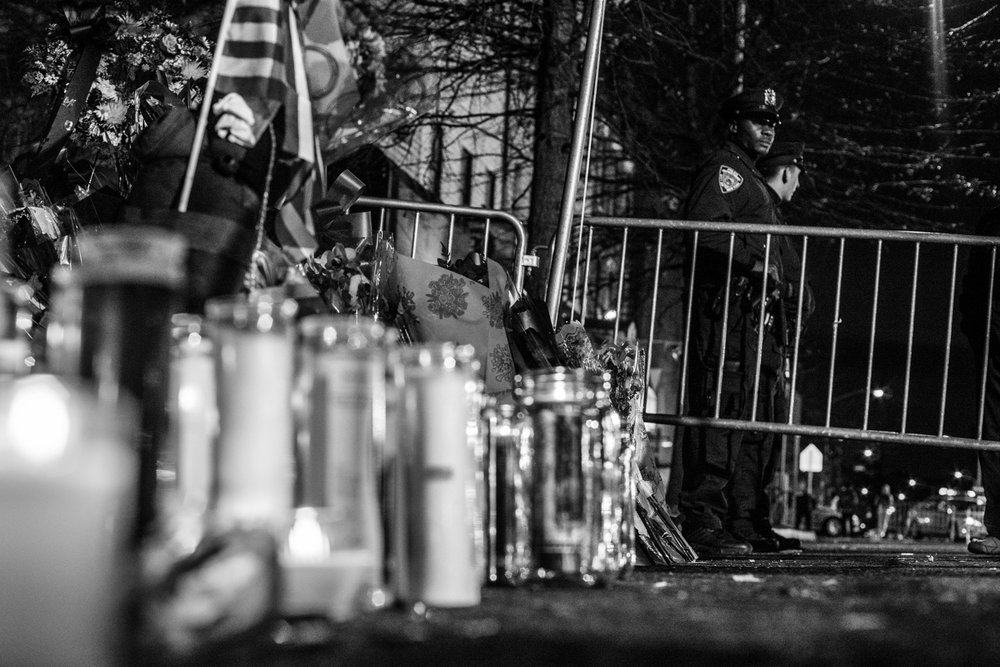 NYPD officers Wenjian Liu, 32, and Rafael Ramos, 40, were sitting in their police car parked near Myrtle and Tompkins avenues in Bedstuy, Brooklyn when both were shot through the window by an attacker claiming to be reacting to the decision not to acquit police for their involvement in the death of Eric Garner.  Flowers and candles mark the spot as NYPD officers look on.  This happened in the same neighborhood as the boxing gym that Nate manages.