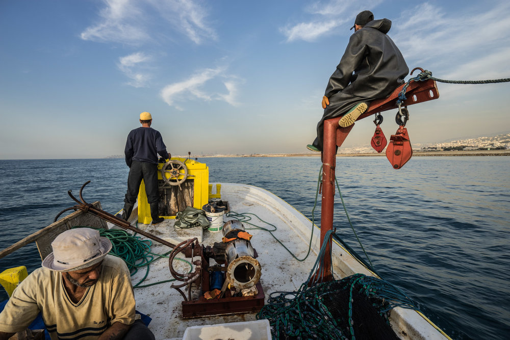 Captain Mohammed (50) steers his fishing trawler while Ibrahim (32) keeps an eye out for fish.  Michel (45) works in the foreground.