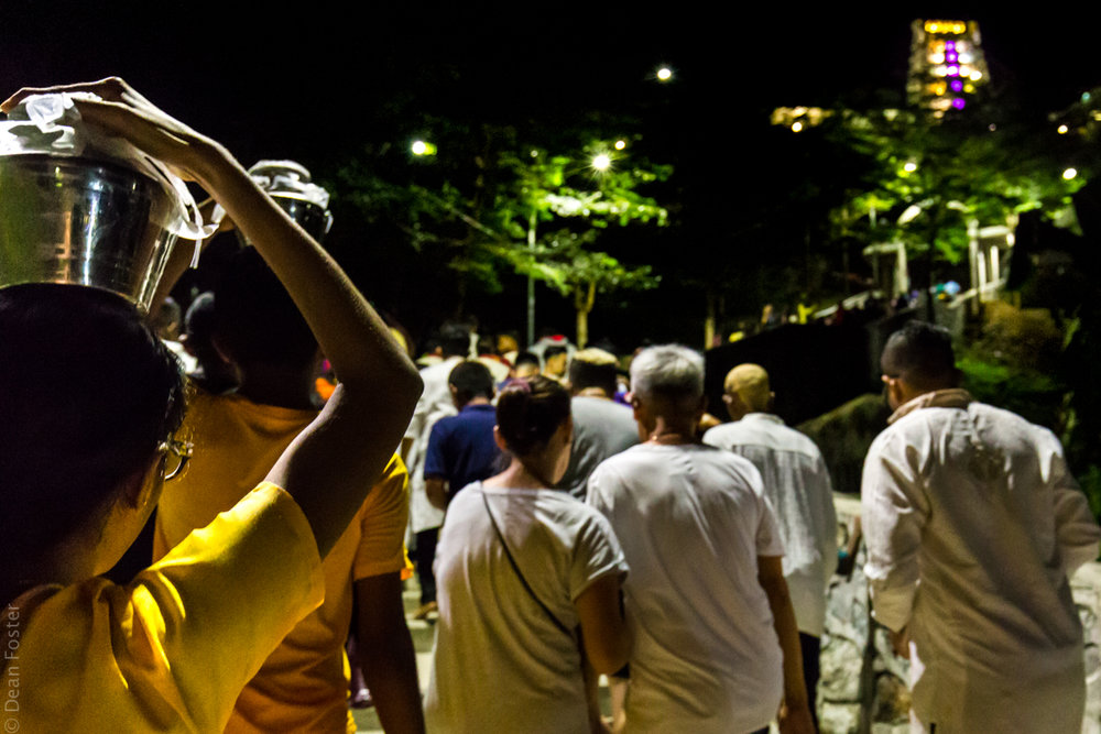 Hindu devotees carry milk up the stairway to the Waterfall Hilltop Temple during Thaipusam celebrations
