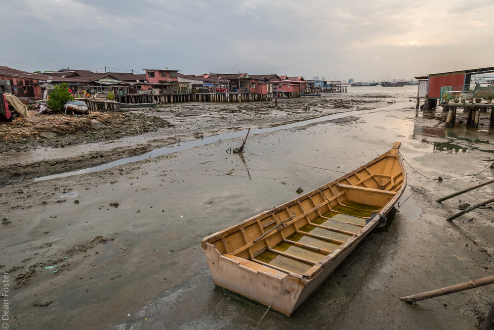 A small boat rests in the mud during low tide along Tan Jetty