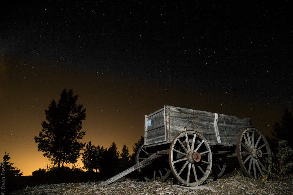 A retired wagon rests under the stars and city lights
