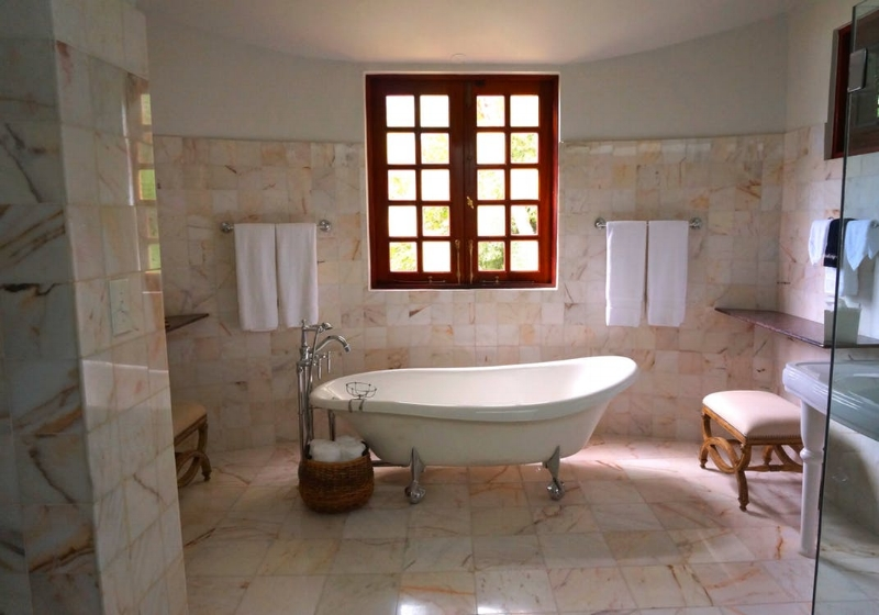 Neutral square tiles support the feature red window frame and classic bath. What tiles? Image source - Pexels.com