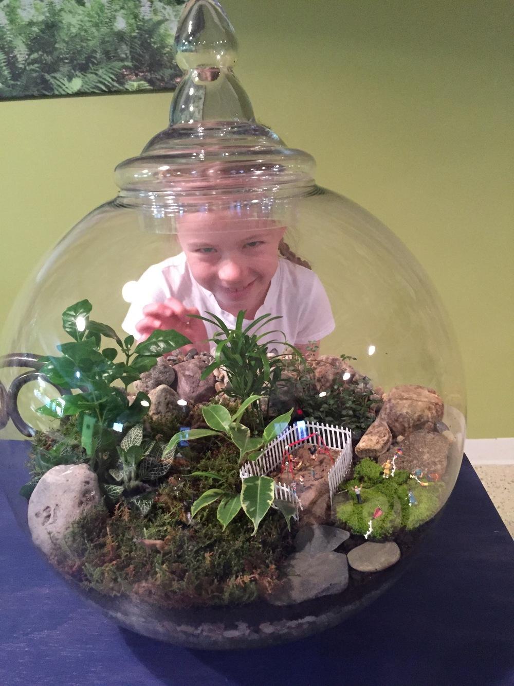 Kathleen's daughter peeking through a huge terrarium.