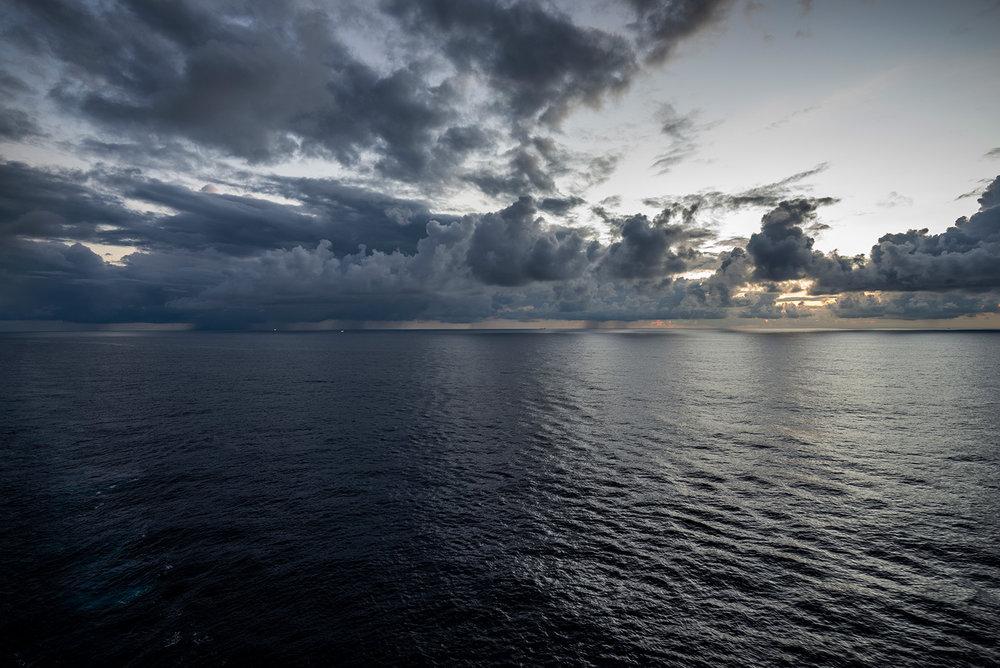 日出一反常态的没有色彩,如同水墨一样。隐约可见雨云下亮着灯的两艘船。(小图可能看不清)