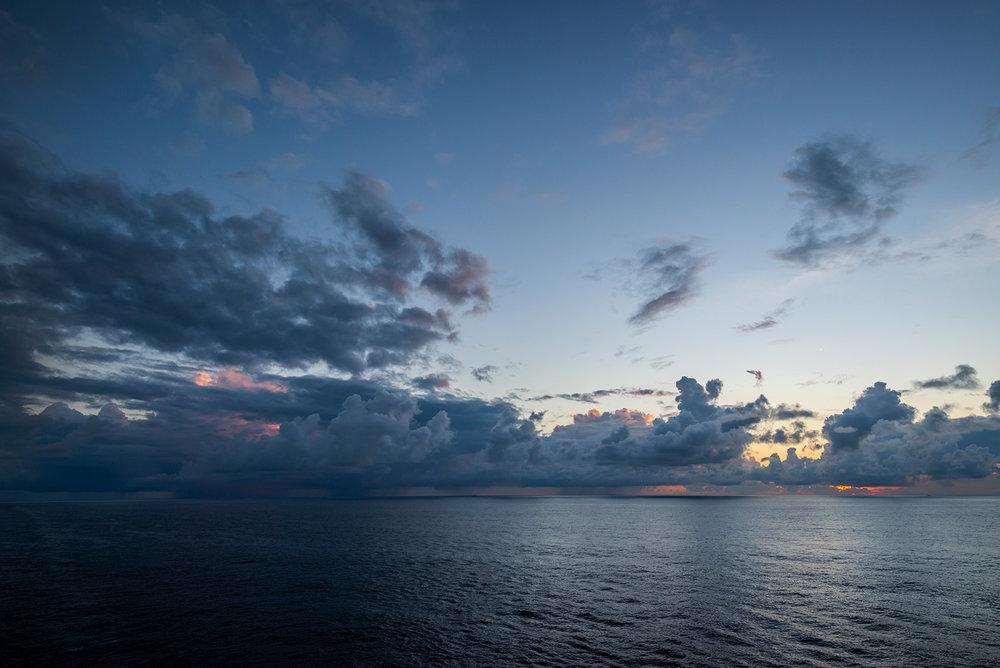 远处的云层彻底挡住了太阳,略微透出了些色彩。
