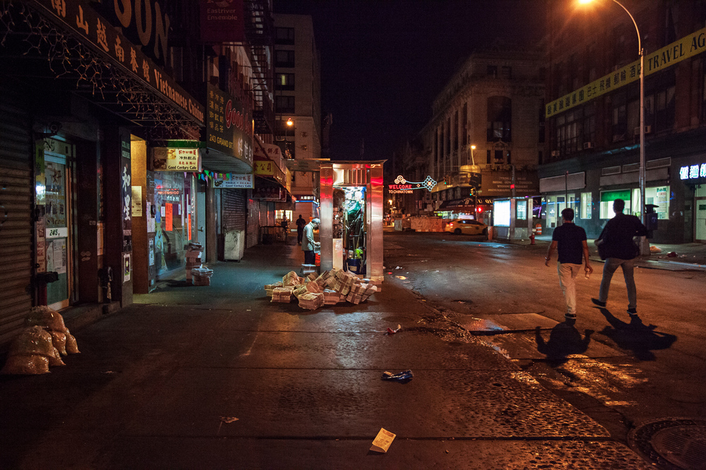 Newspaper cart opening up for business as late nighters head home at 5am, China Town, NYC