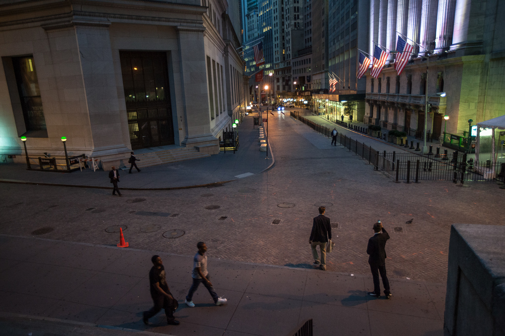 People on Wall Street just before sunrise