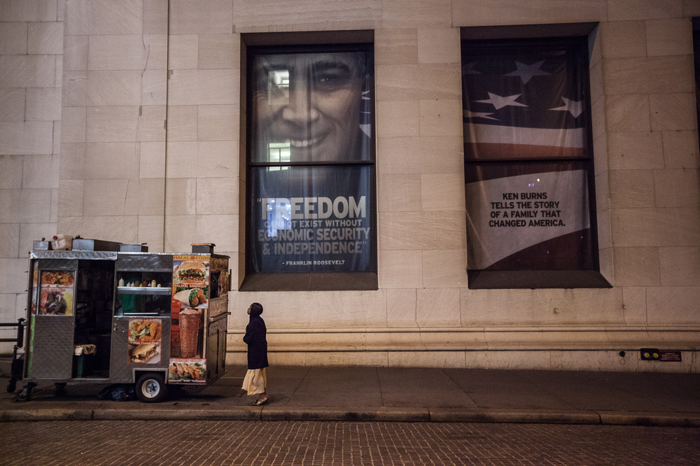 A woman in her nightgown, buying a cup of coffee from a cart on Wall Street at 5am