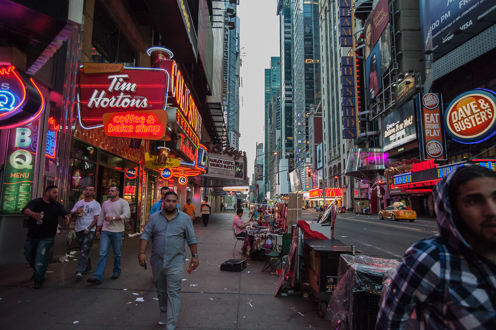 John, who sells photos to tourists, arrives in Time Square very early to set his table up for the day, while a few men leaving a bar stumble past 6:15 am.