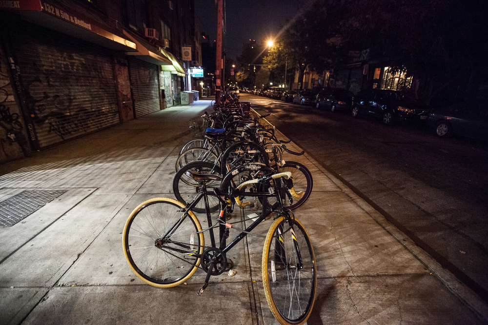 Bikes locked up off Bedford Ave in Williamsburg, Brooklyn. Normally a very busy sidewalk, sits empty at 6 am.