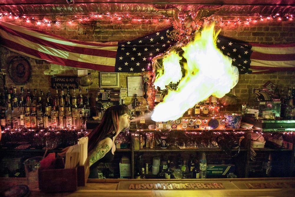A bartender in Time Square, New York City blowing fire to entertain patrons.