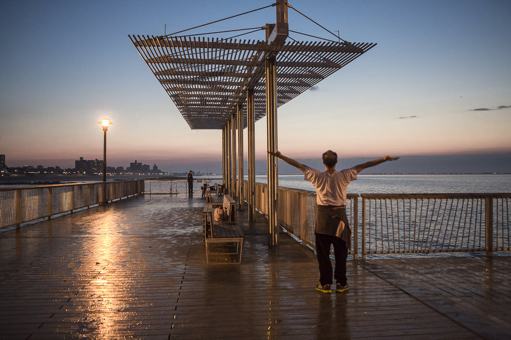A runner stretching on the Coney Island Pier, Brooklyn NY at 6 am.