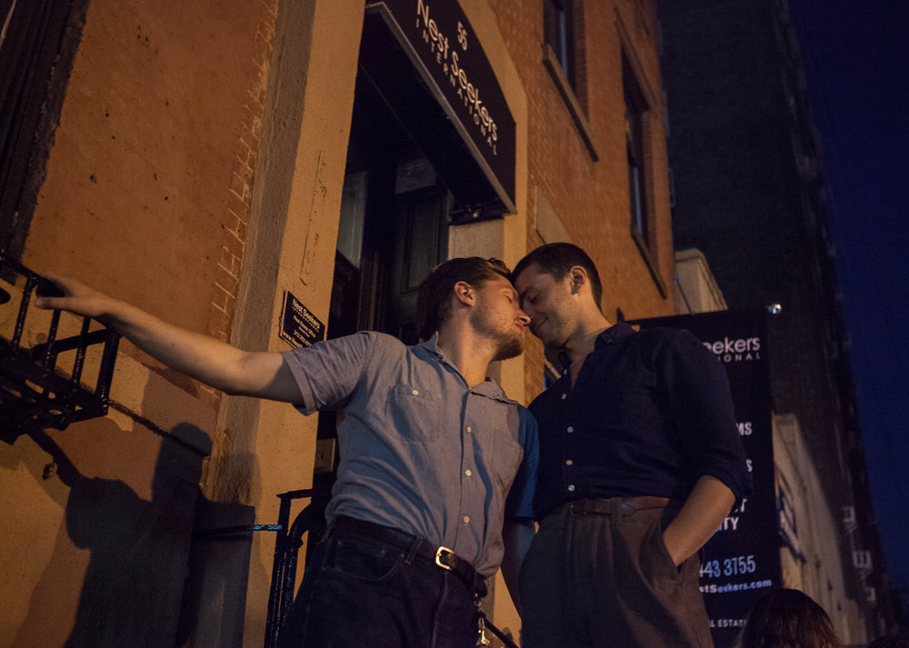 A couple leans in close outside of the historic Stonewall Inn, in New York City, birthplace of the Gay Rights Movement.