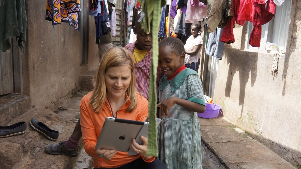Showing kids photos of themselves on an iPad in Nairobi
