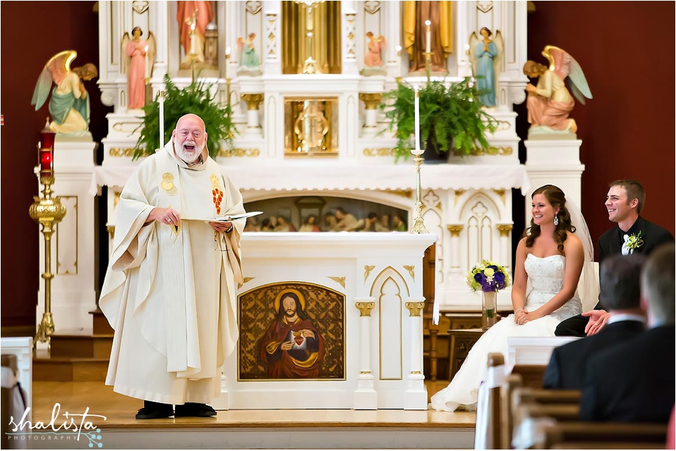 Priest laughing during wedding ceremony.