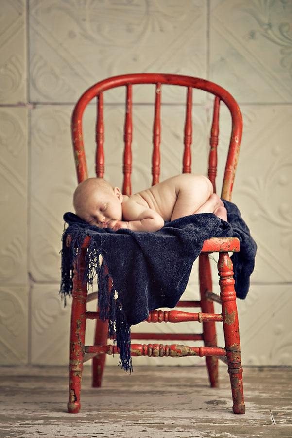 Newborn baby on a chair.