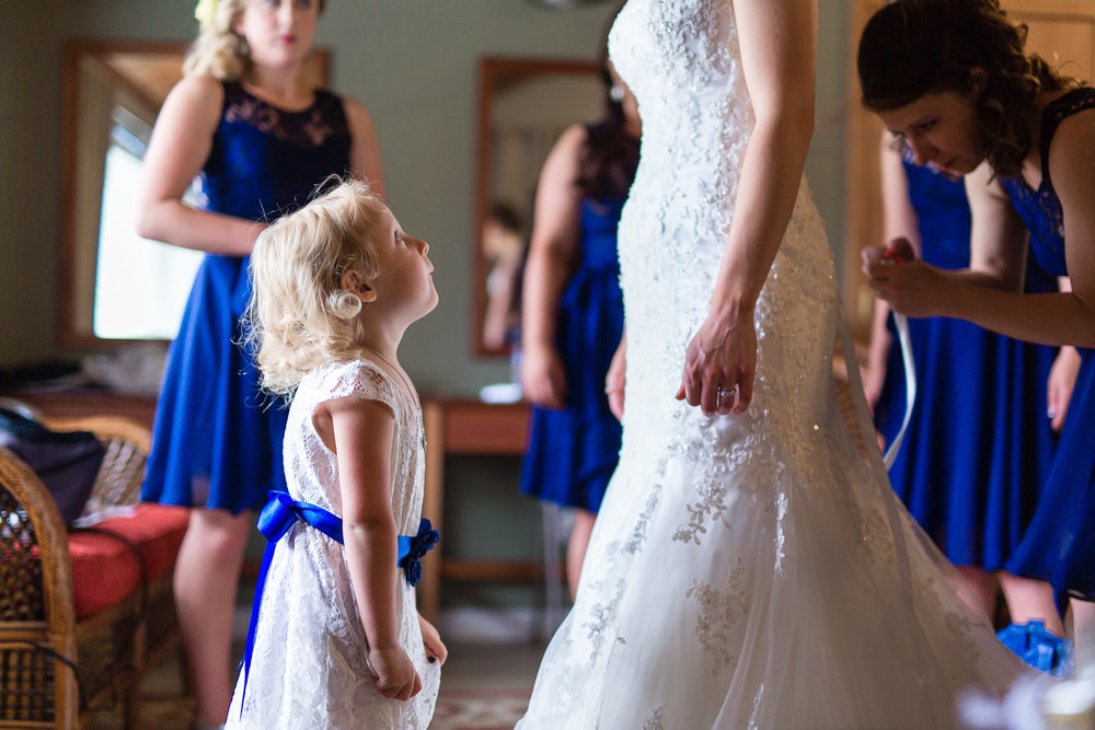 Flower girl looks up at bride in wedding dress