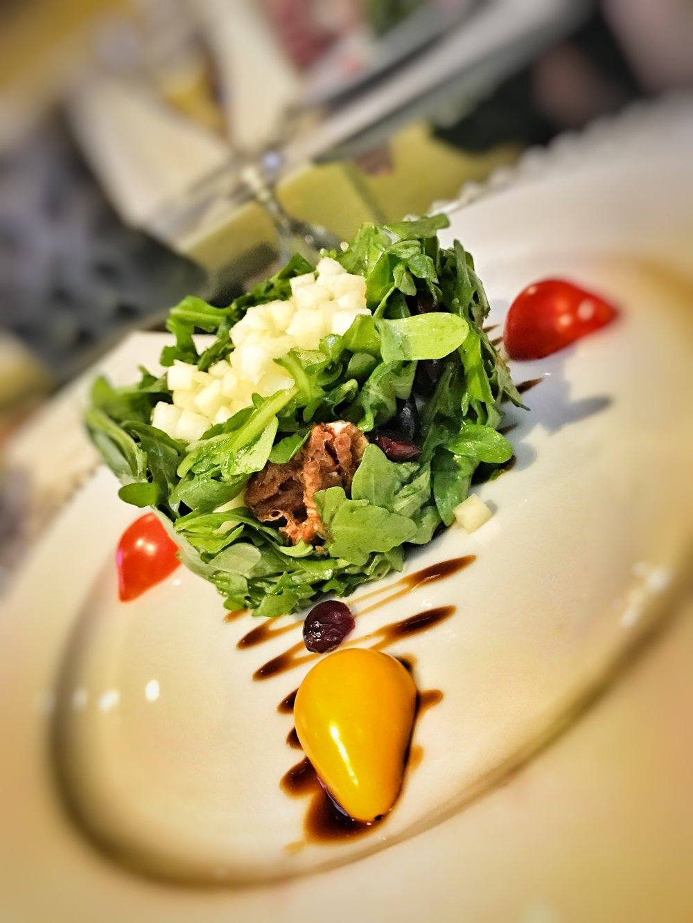 COMPRESSED SALAD OF BABY ARUGULA with MANCHEGO CHEESE, GALA APPLES, SUNDRIED CRANBERRIES, CARAMELIZED PECANS & TEARDROP TOMATOES with AGED BALSAMIC VINAIGRETTE