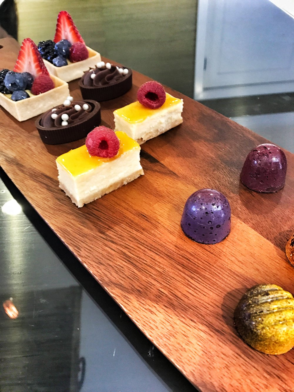 ASSORTED MINIATURE PASTRIES - BLACKBERRY TRUFFLE, CHOCOLATE MOUSSE CUP, MINI CHEESECAKE, AND FRESH FRUIT TART