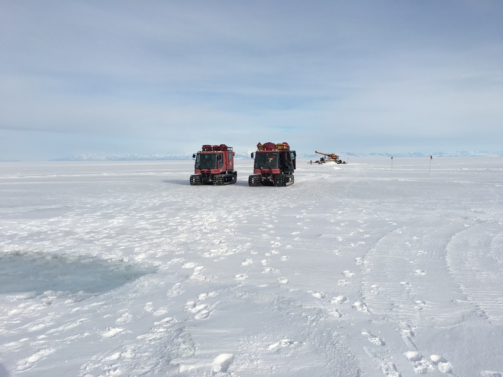 Two pisten bully on the ice with the drill rig in the background.
