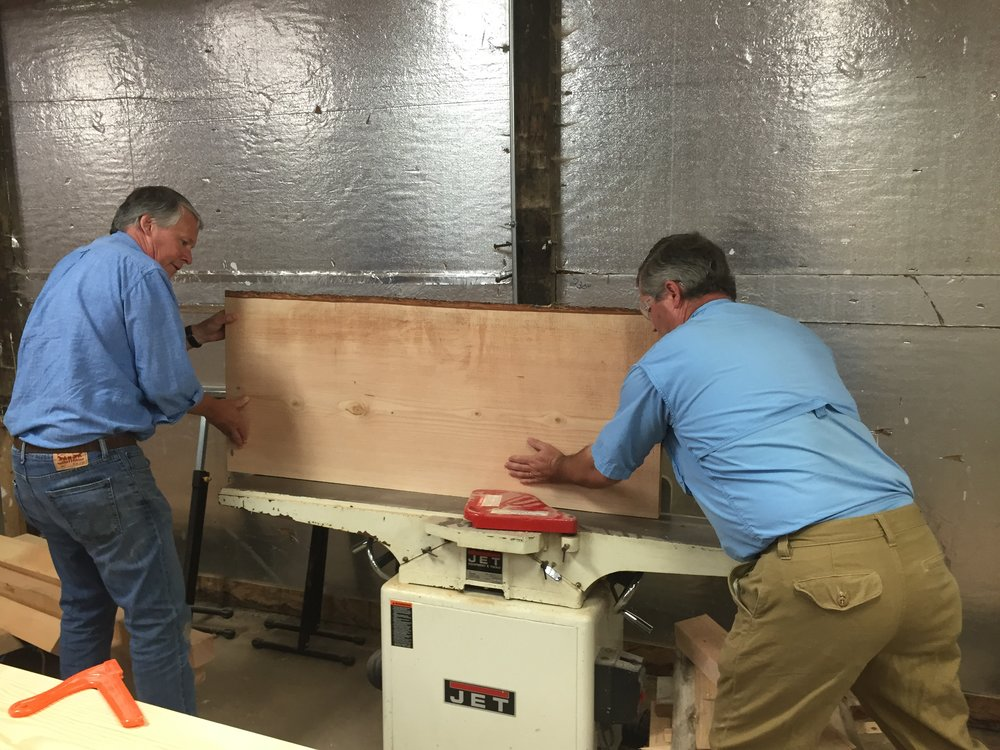 We provided the desk and table tops for Port Blakely, but the bases of the desk and meeting table were constructed by another company. For this project, my dad and I learned how to joint the wood. In this picture, our good friend Cort is showing my dad and I how to use the jointer we bought a few months ago. This machine allows us to get the straightest cut possible so the wood slabs will line up perfectly.