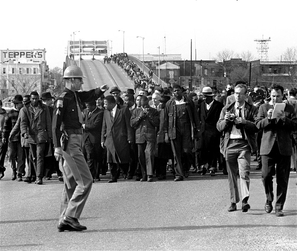 Here he is on Edmund Pettus Bridge writing on a notepad, the crush of the march behind him and his photographer, a National Guardsman high stepping it to their left. I love this photo, mostly for the men in the front wearing sharecropper overalls in solidarity with black farmers. (The Associated Press)