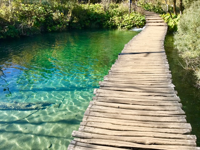Walking over crystal clear Plitvice Lakes.