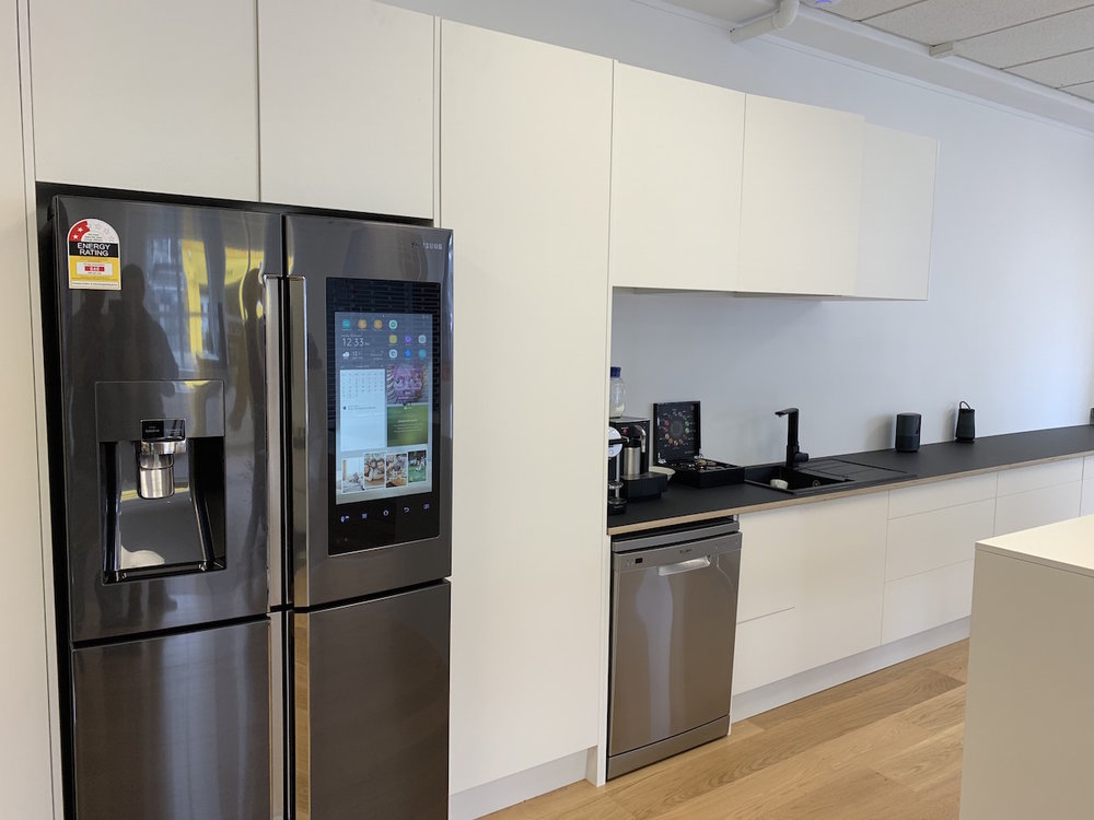 The demonstrator kitchen, complete with Smart Samsung fridge. Benchtops made from Polaris 24mm Black from Plytech with a European Birch edge detail.