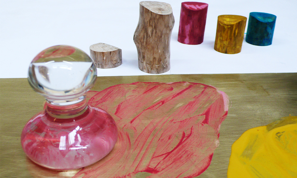 'I made up different powder mixes with the earth pigments using an egg, linseed, pigment and water. I used the tree trunks objects in the picture to test different paint recipes along with writing down the mixes in a notebook. I used the glass knob as a pestle on a brass base to grind the grit out of the pigment to make the paste.'