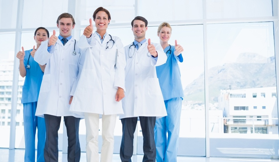 Group portrait of young doctors gesturing thumbs up at hospital.jpeg