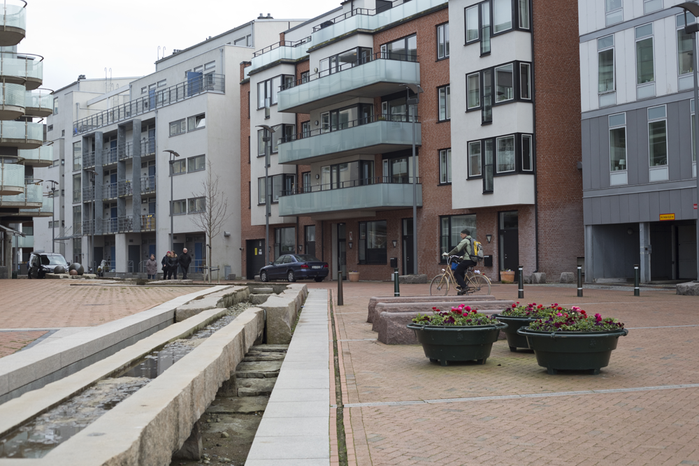 Five-story apartment buildings line the larger public spaces leading to the waterfront. Cars are welcome as slow-moving guests in pedestrian and bike-friendly territory.