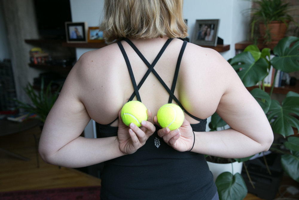 1. - Place the tennis balls between your shoulder blades, on either side of the spine.