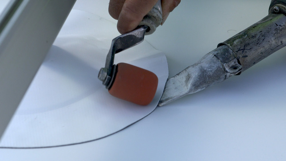 Heat welding the flashing membrane skirt directly to the roof membrane. Photo - Tom Miller