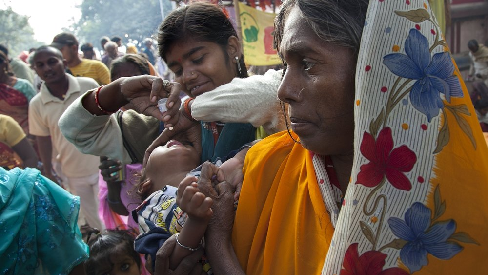 A health worker administers the polio vaccine to a child during the crowded Sonepur Cattle Fair (Malegaon Mela) in Bihar, India.