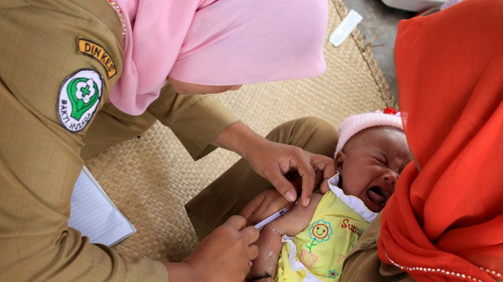 An infant receives a vaccine injection as part of a government program in Panyabungan, Indonesia.