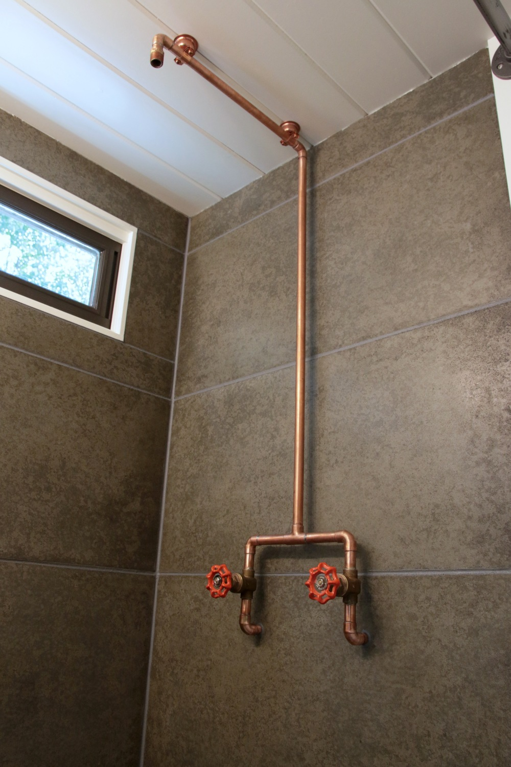 The Phoenix by Wind River Tiny Homes. Custom concrete shower tiles. Exposed copper shower pipes.
