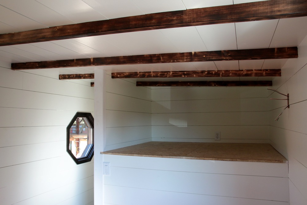 The Phoenix by Wind River Tiny Homes. Exposed charred rafters in storage space above the bathroom. Access from bedroom.
