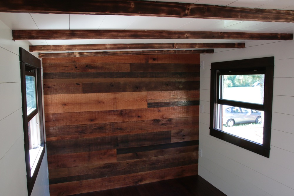 The Phoenix by Wind River Tiny Homes. Reclaimed pallet accent wall in the bedroom.