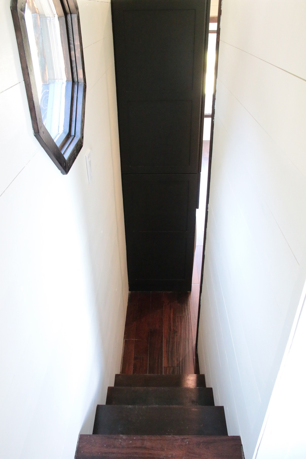 The Phoenix by Wind River Tiny Homes. Storage stairs from loft leading to main living space.