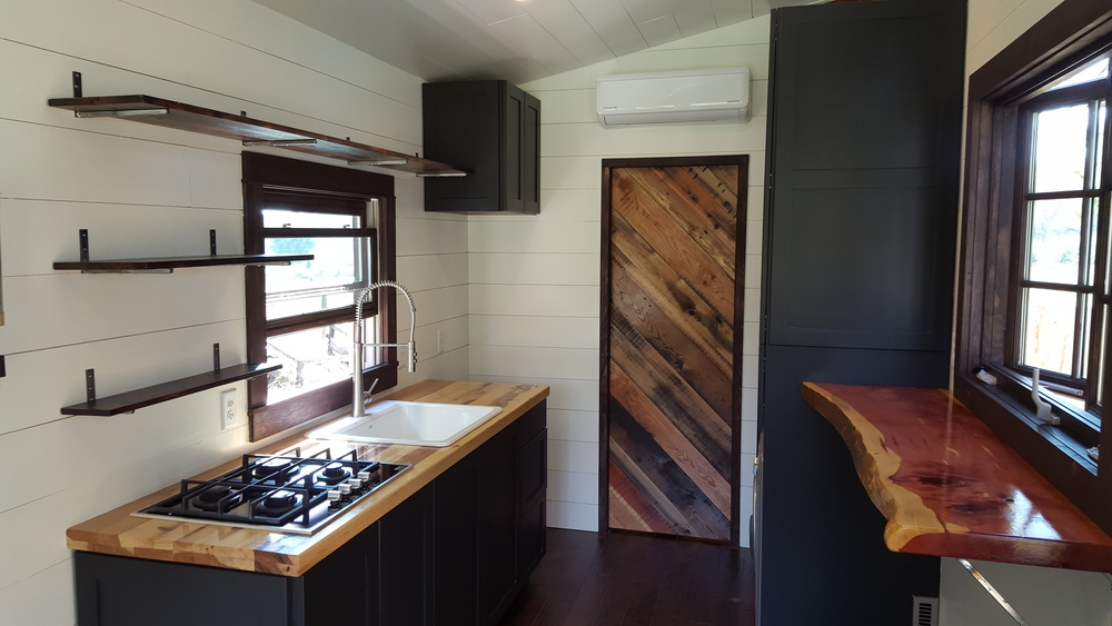 The Phoenix by Wind River Tiny Homes. Hickory butcher block countertops, custom shaker style cabinets, reclaimed wood pocket door, live edge cedar bar top.